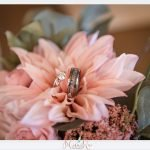 Wedding ring and band posed in pink wedding bouquet