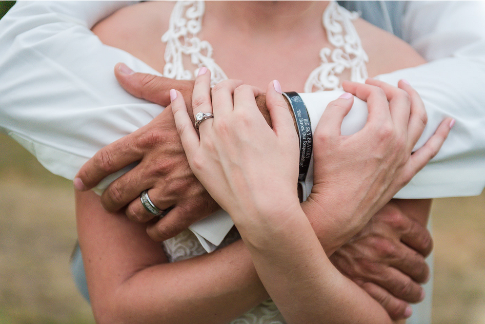 Close-up of bride and groom's handing linked together in front of brides body showing rings and grooms' military bracelet