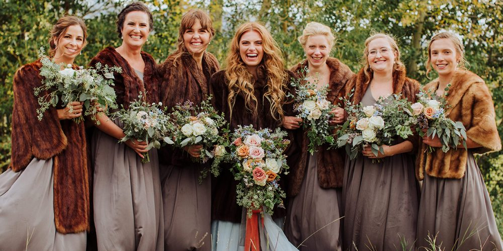 Bride in line with her bridesmaids with shalls and flowers