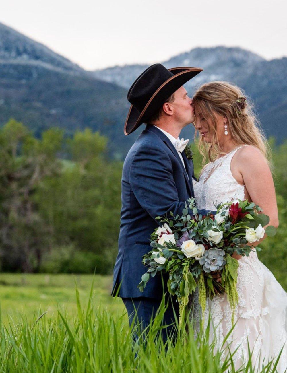Cowboy kissing brides forehead