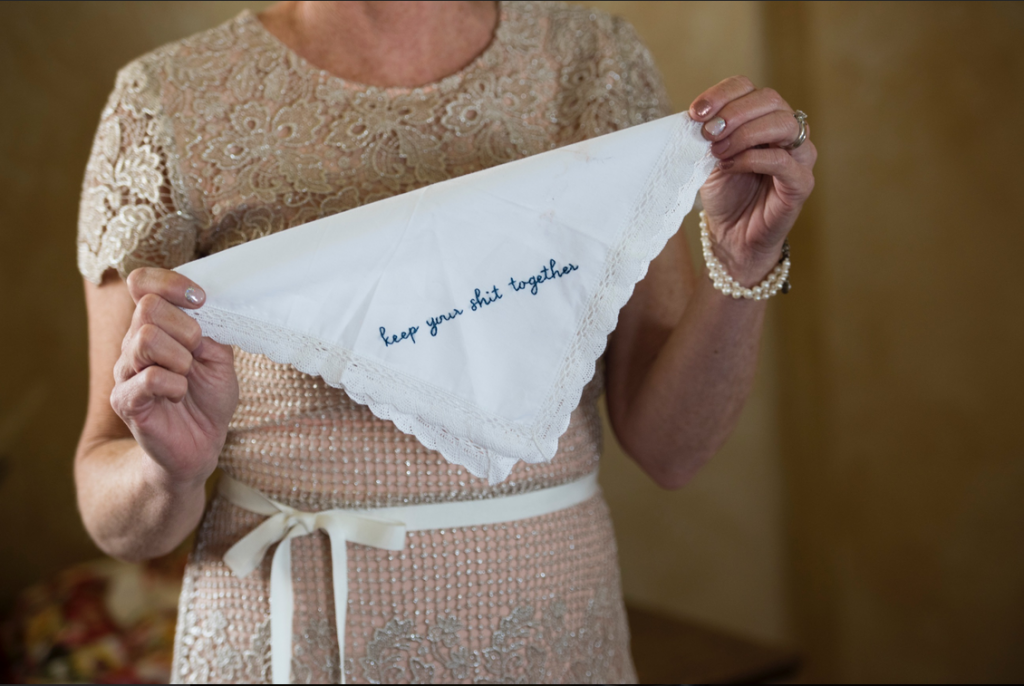 "Mother of the bride holding a white custom embroidered handkerchief that says ""keep your shit together"" in blue thread"