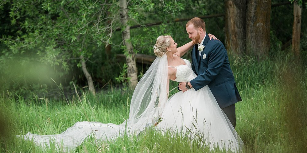 Groom dips bride in green field at Hart Ranch