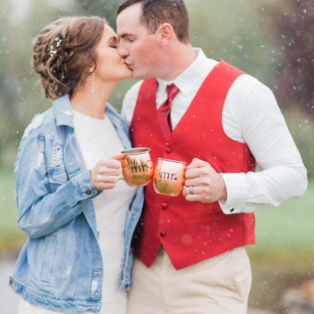 Bride wearing denim jacket and groom in red vest kissing in the snow and toasting with Mr. and Mrs. copper cups