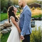 Bride and groom face each other in front of a pond at the Hart Ranch