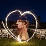 Bride and groom make heart shape with sparklers in front of Hart Ranch Weddings' Two Heart Chapel at night