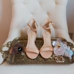 Wedding detail close-up with blush single strap heels, wedding rings, garter, and perfume bottle on vintage tray.