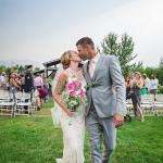 Bride and groom kiss at end of wedding aisle at Hart Ranch