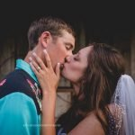 Bride passionately kissing groom while touching his jaw with left hand