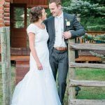 Groom smies at his bride while he leans on a fence post and pulls in his bride with his right arm.
