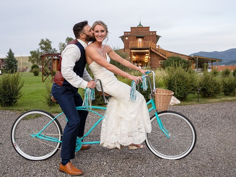 Bride and groom on teal tandum bike with Hart Ranch Wedding's Barn in background