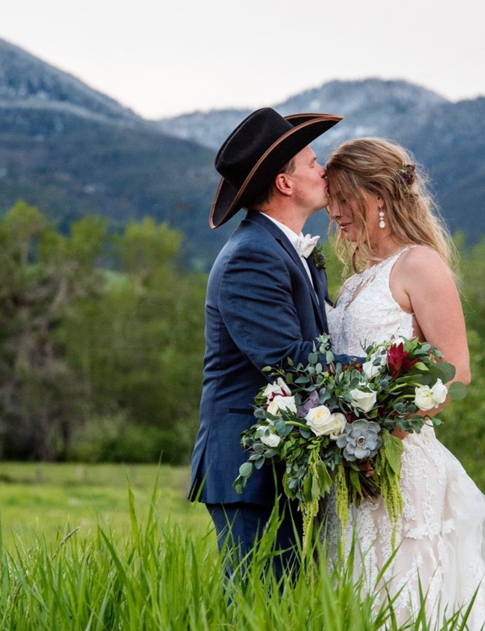 Cowboy kissing brides forehead