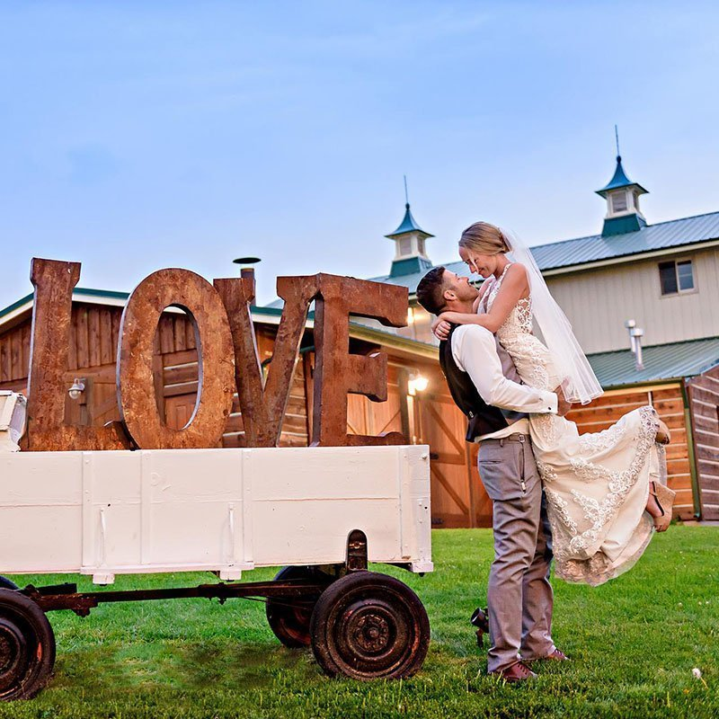 Groom picking up bride next to love wagon in front of Hart Ranch barn