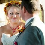 View over groom's left shoulder of smiling bride with flower crown