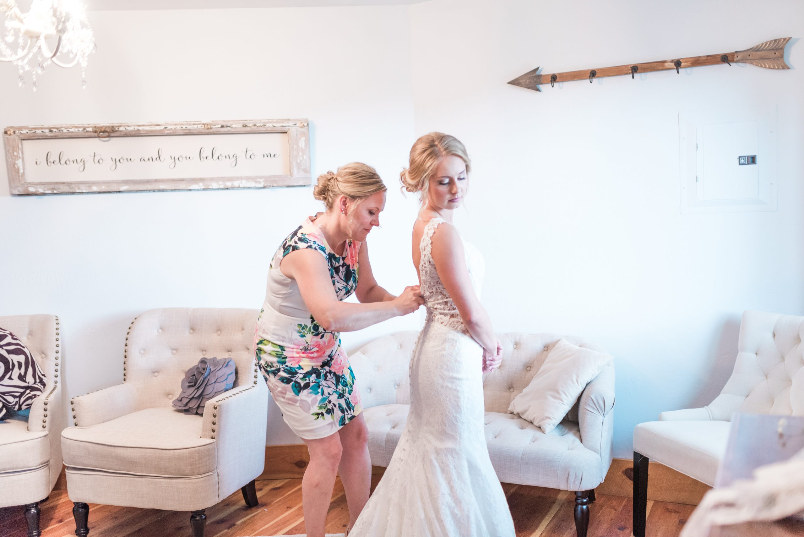 Mother of the bride helps her button up the back of her wedding dress